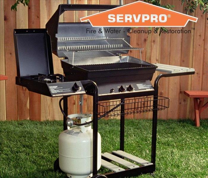 Apropane grill sitting in a yard with a wooden fence and the SERVPRO logo.