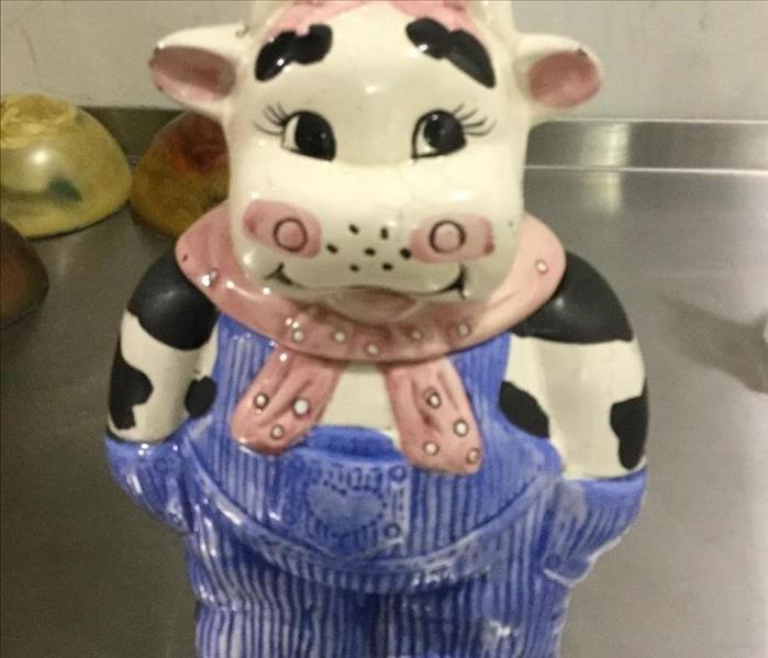 A cow cookie jar cleaned after a fire damage.