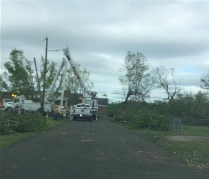 Destuction and debris from the tornado that passed through while line men work to restore power.