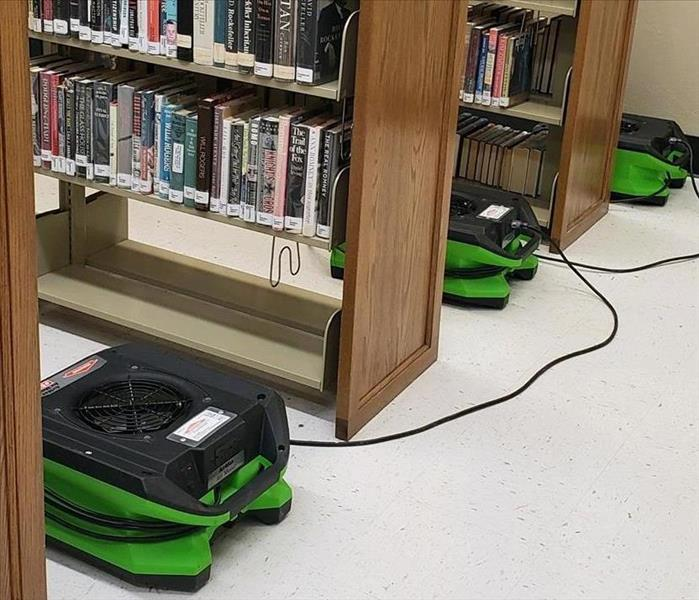 SERVPRO air movers set between the aisles of a library.